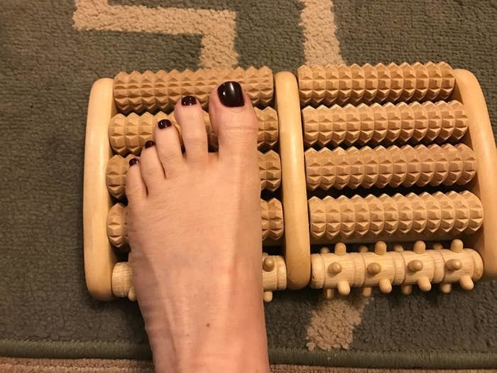 reviewer's foot on the small roller foot massager