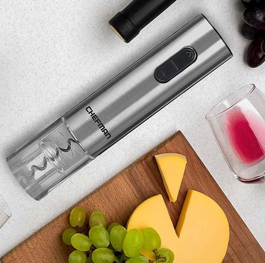 The electric wine bottle opener next to a cheese plate
