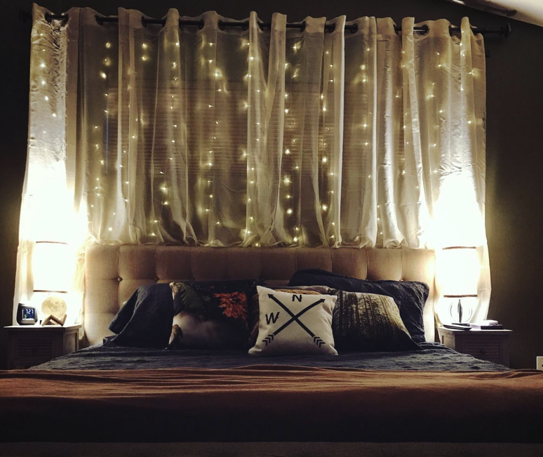 a reviewer's room with twinkle lights hanging behind their bed