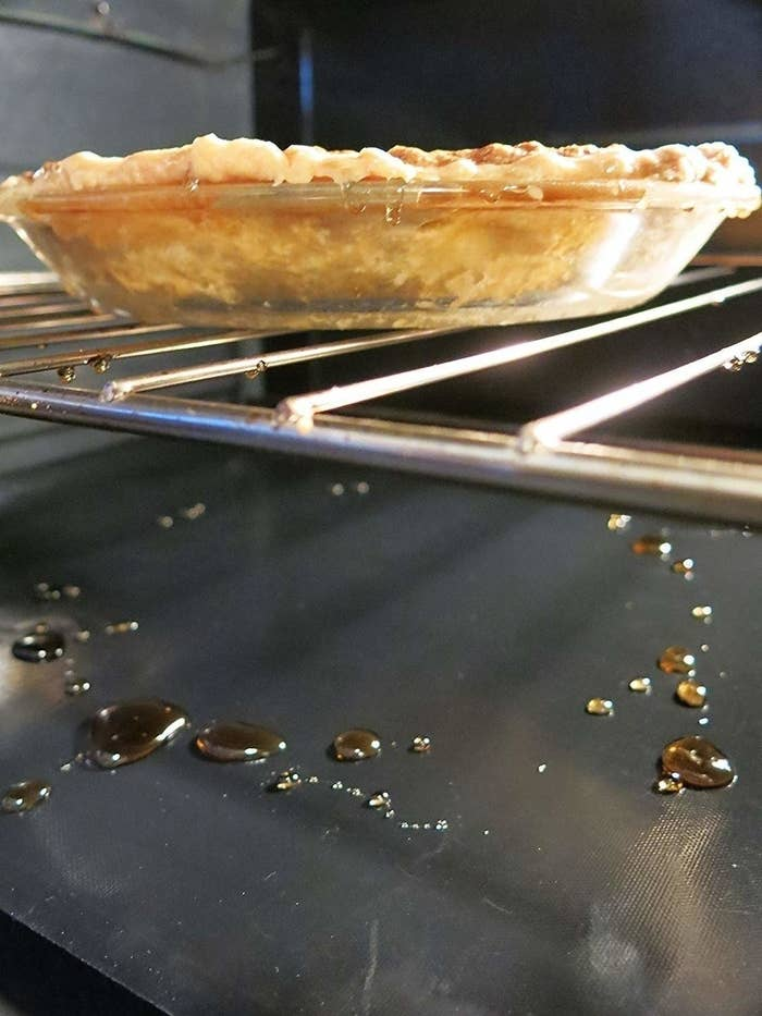the oven liner underneath a pie collecting drippings