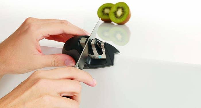 someone using the small, handheld knife sharpener