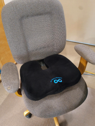 a reviewer's office chair with the u-shaped black seat cushion on it