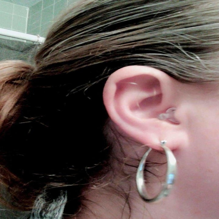 A close-up of it in a reviewer's ear; the clear tail very nearly blends in