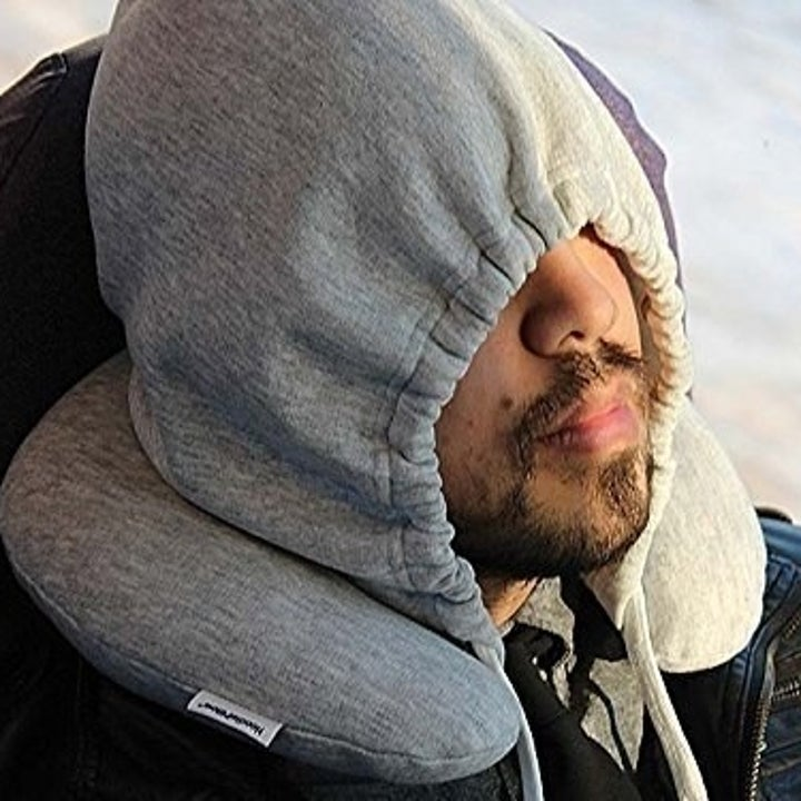 The same model with the hoddie pulled down over their eyes, to block the light