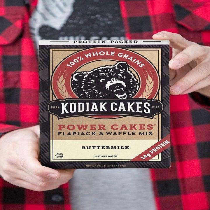 hands holding the box of Kodiak Cakes Power Cakes