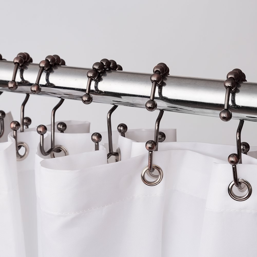 Double-sided shower hooks hung on a rod with a curtain strung on one side and a liner on the other