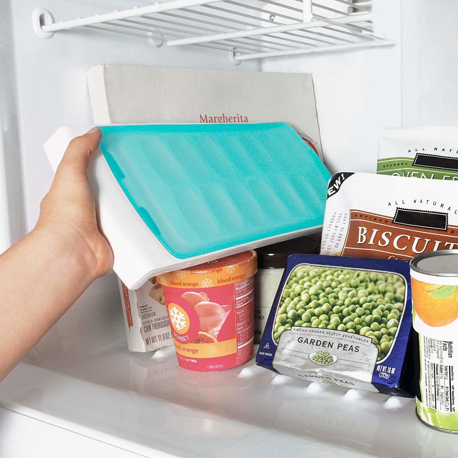 A hand placing an ice cube tray with a lid into a crowded freezer