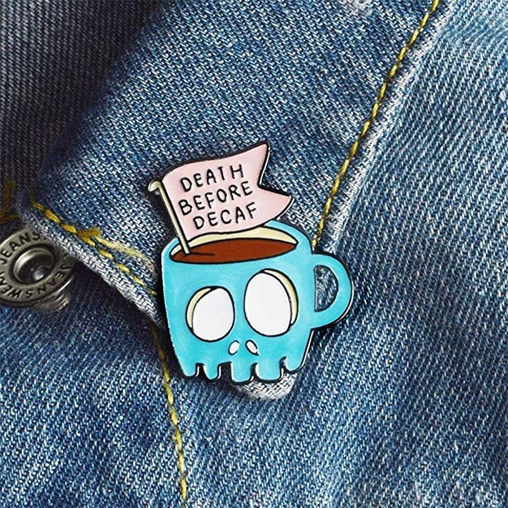 """a closeup of a brooch that says """"death before decaf"""""""