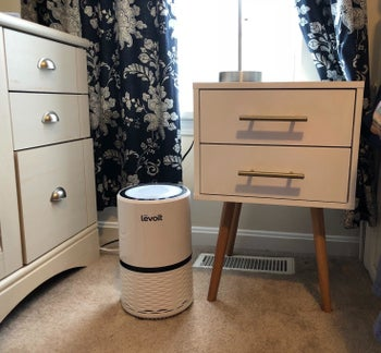 The air purifier in white sitting next to a nightstand