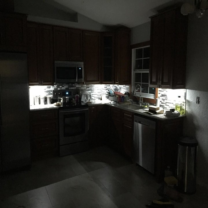 Kitchen cabinets in a dark room with bright under-cabinet lighting