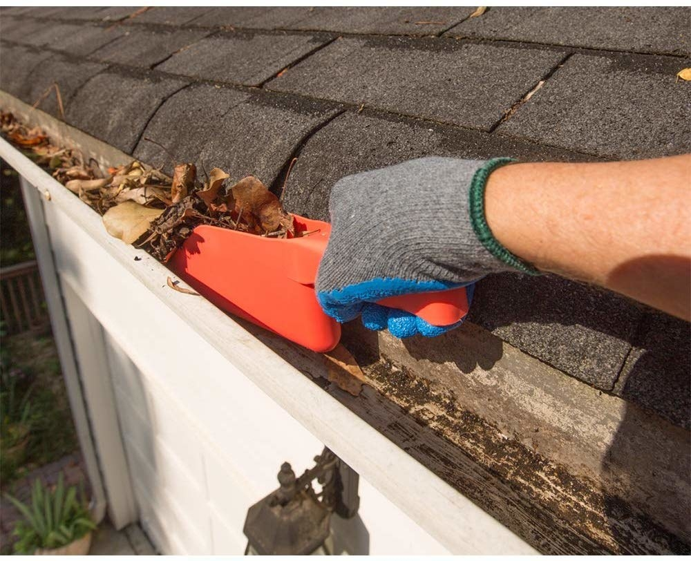 A hand using the orange narrow scoop to clear leaves out of a gutter