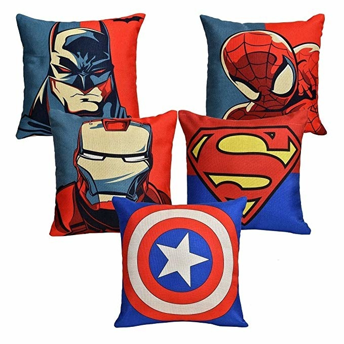 Five pillows with pillow covers that have Batman, Spider-Man, Iron Man, the Superman symbol, and Captain America's shield on them respectively