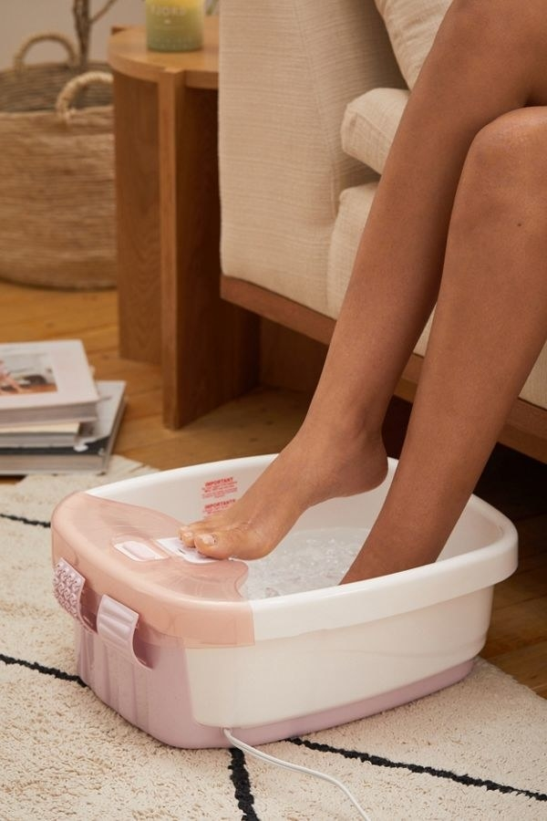 The square-shaped foot bath with rounded edges and water in it with two feet in it