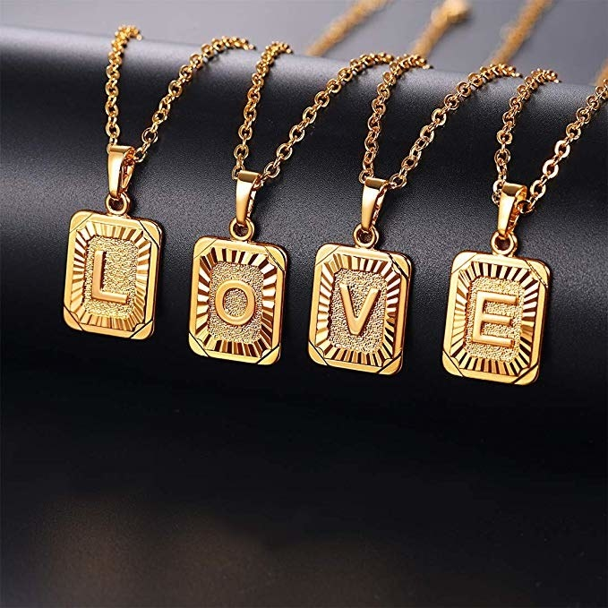 Four gold rectangle pendants on chains with the letters 'L, O, V, E' on them