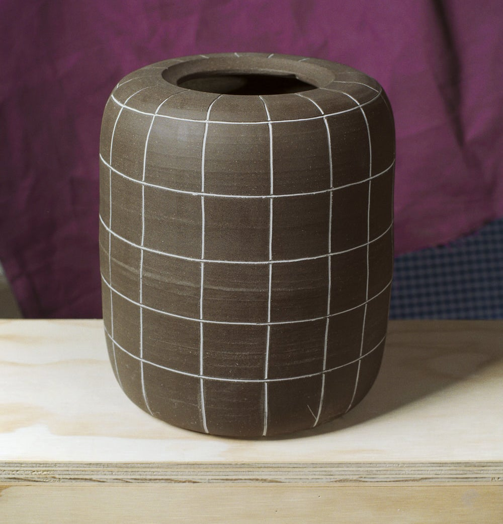 A tall, spherical brown vase with white windowpane etching