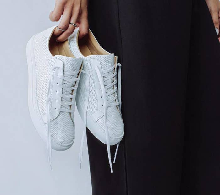 hand holding the white sneakers with white soles and laces