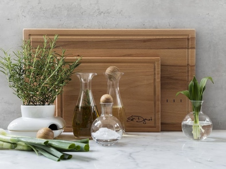 Three glass carafes with round oak stoppers on a countertop next to various leafy plants and in front of two standing wooden cutting boards