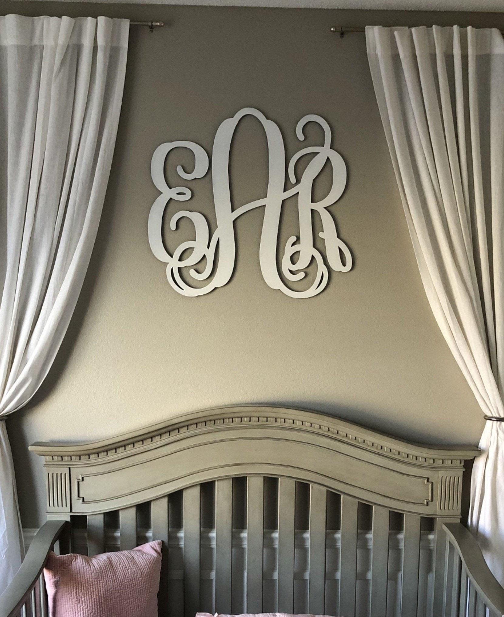 a white wooden monogram over a crib