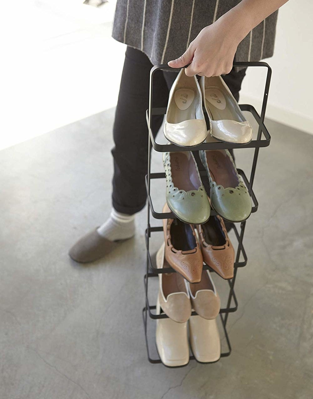 the lower half of a model holding a tiered shoe tower by the top handle