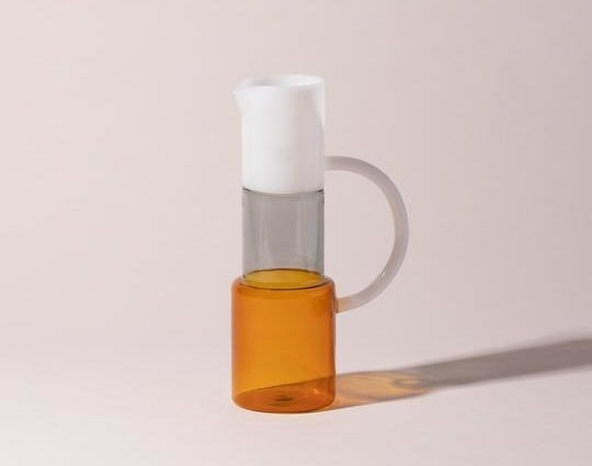 A slim glass pitcher with an amber bottom, clear middle section and white top