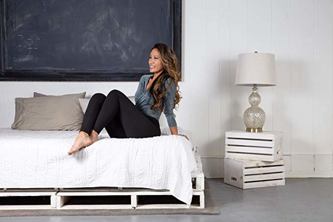 model wearing the leggings, sitting on a bed