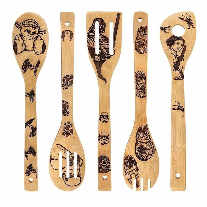 four wooden kitchen utensils with Starwars characters and objects engraved in black. From left to right: Spoon with Yoda, Stormtrooper, Darth Vadar, Chewbacca, and Princess Leia