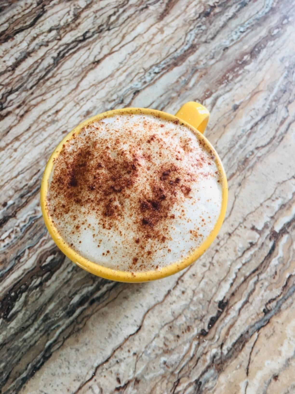 A reviewer's frothy latte dusted with cinnamon