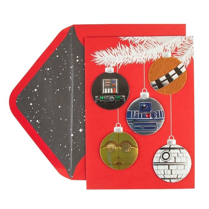 a red card with five ornaments on it shaped like different Star Wars characters and objects