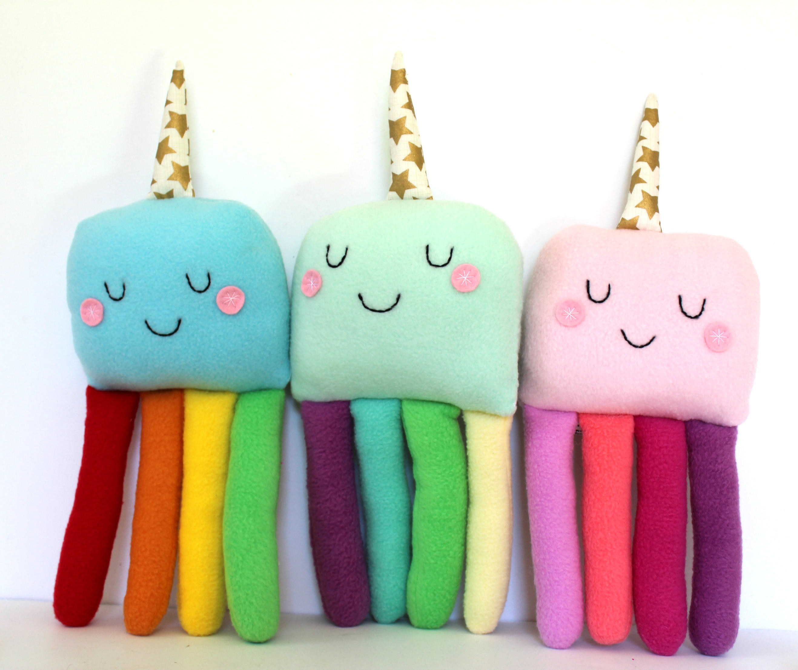 different colored cute plushes with a unicorn horn and four tentacles each