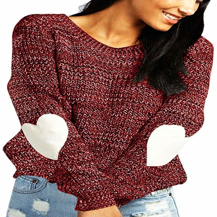 a model in the burgundy sweater with white hearts on the elbows