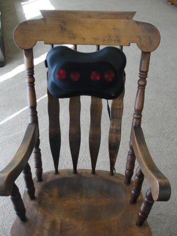 The massager strapped to the back of a chair