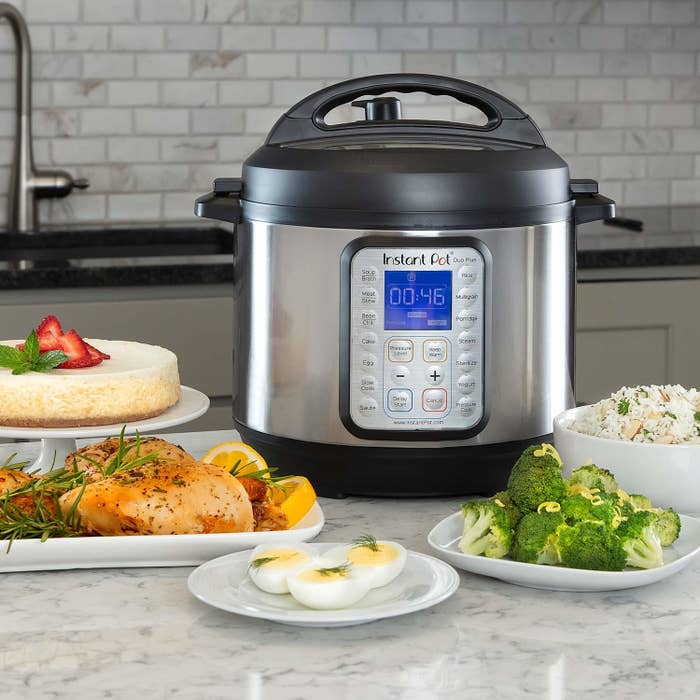 An Instant Pot with plates of food around it