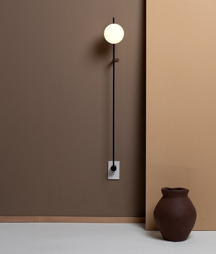 A vertical wall lamp plugged into an outlet with a glowing orb at the top