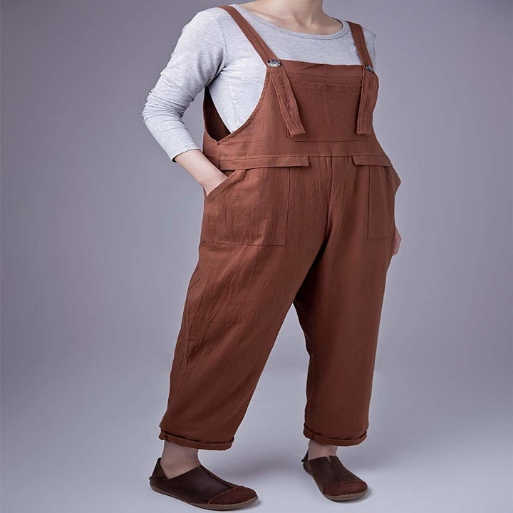 Model wearing a pair of brown overalls over a gray long sleeve T-shirt