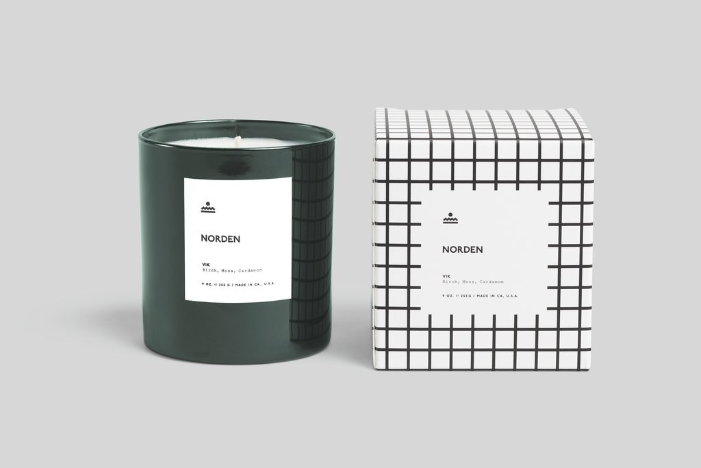 A Norden branded candle in a dark green glass votive next with a white and black box with a windowpane print