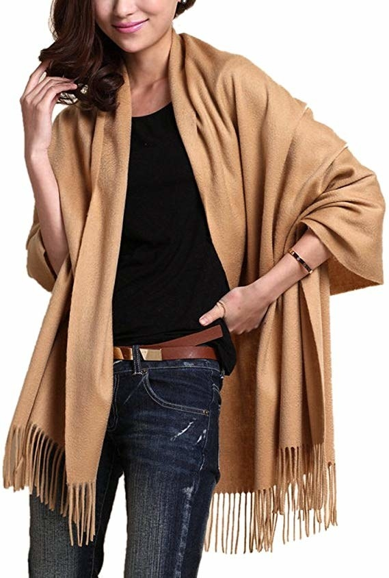 A model wearing the cashmere and wool shawl in tan.