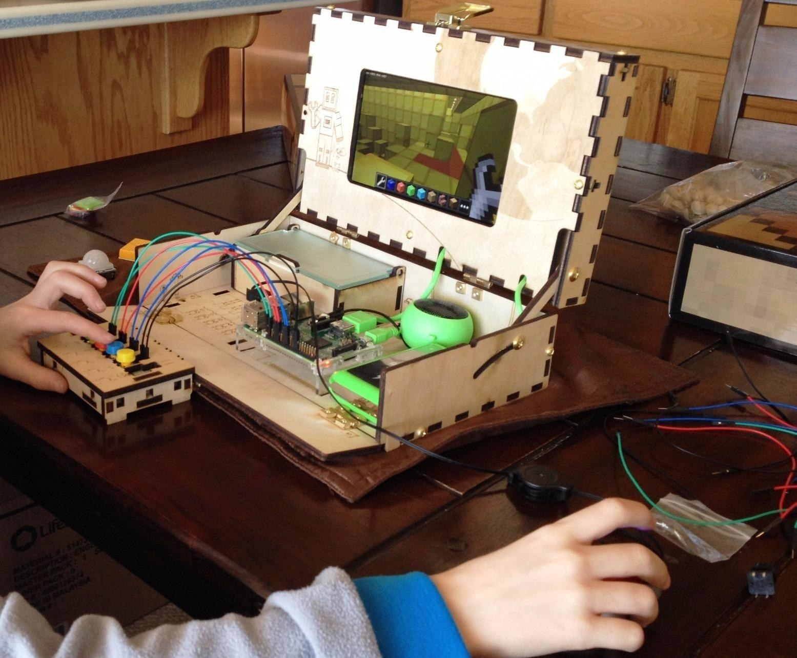 A reviewer's kid using the DIY computer, which looks like a box with wires attached and functioning buttons and a screen