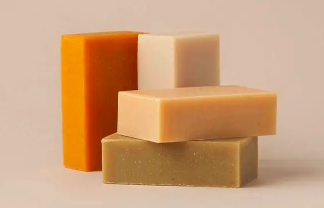 A stack of four different-colored shampoo soap bars