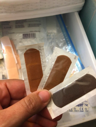 reviewer hand holding three different bandages of varying brown and black skin tones