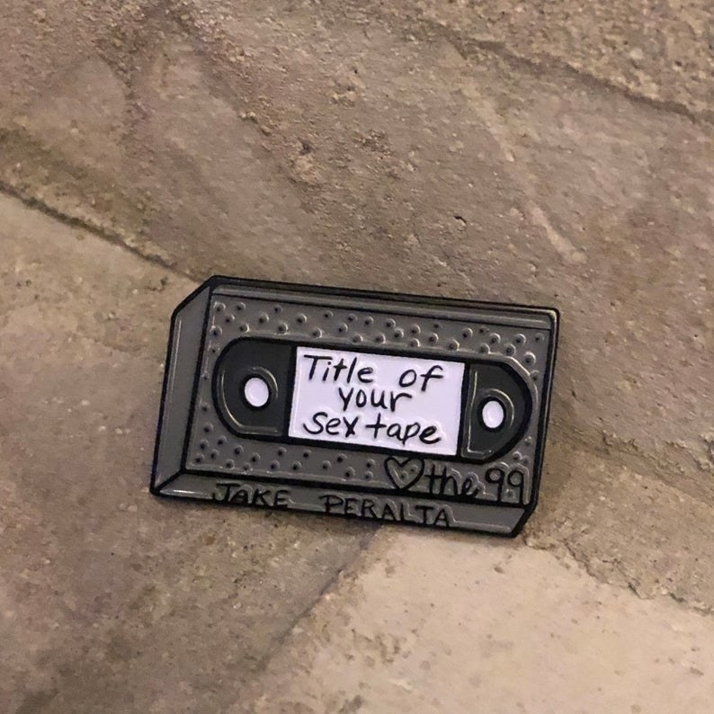 "The VHS-shaped pin that says ""title of your sex tape"" ""Love the 99"" and ""Jake Peralta"""