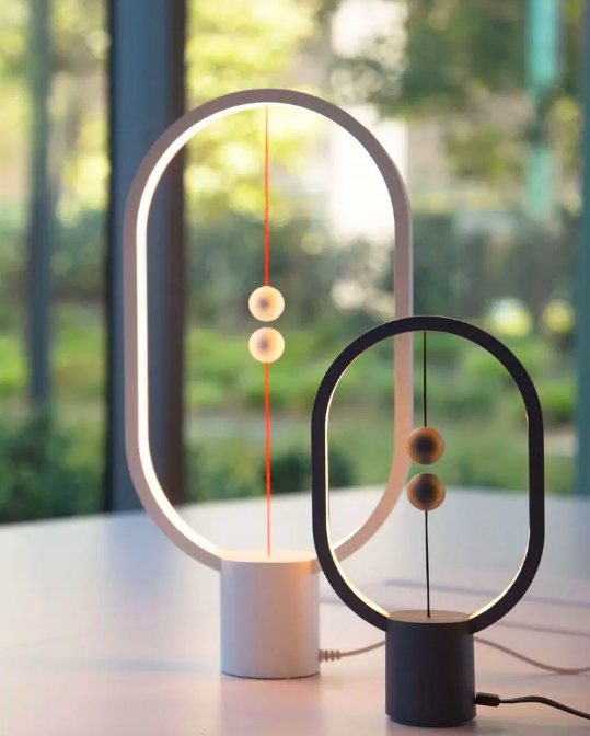 Oval light rings with center base and two magnetic balls attached to strings on top and bottom of light