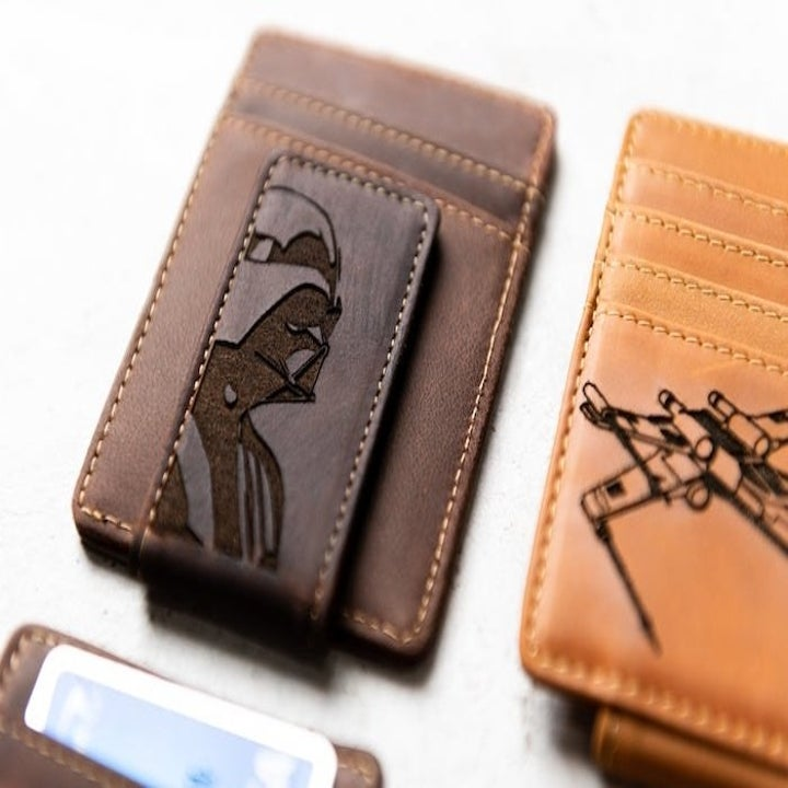 close-up of a dark brown wallet with a money clip with Darth Vadar on it