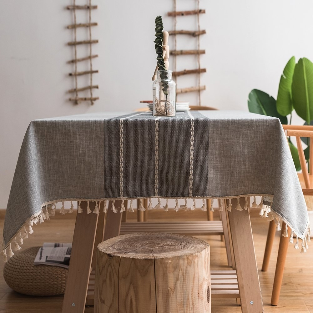 Two tone gray tablecloth with embroidered details down center and tassels on edges