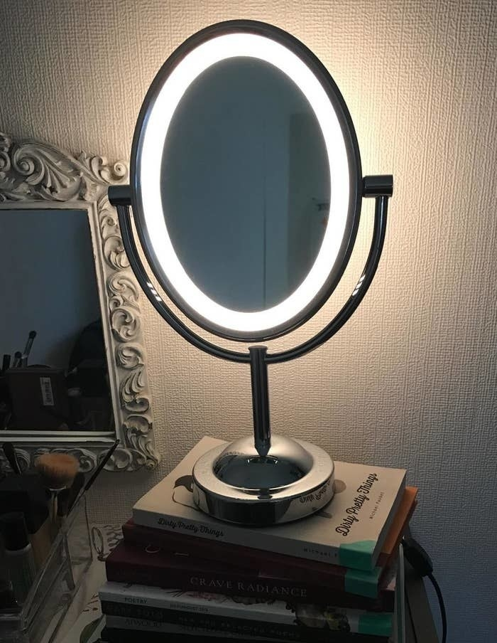 reviewer's round makeup mirror with the light on around the trim