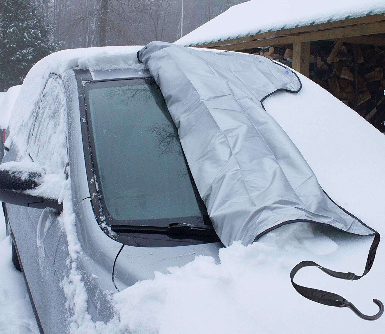 The cover, partially removed from a windshield of a car covered in snow, showing how the windshield is totally snow-free under the cover