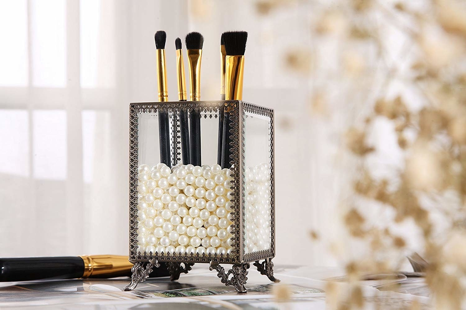 Rectangular glass box with ornate legs and edges in victorian style with faux pearls on inside of box, holding up makeup brushes