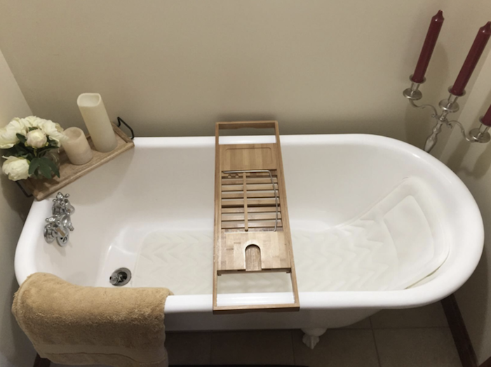a bathtub with the long body pillow laying in the bottom and coming up the back to support the back