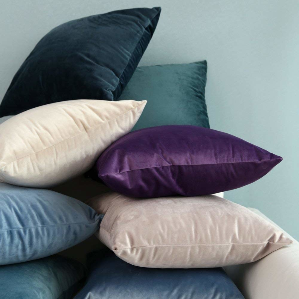The velvet pillows stacked ontop of each other.