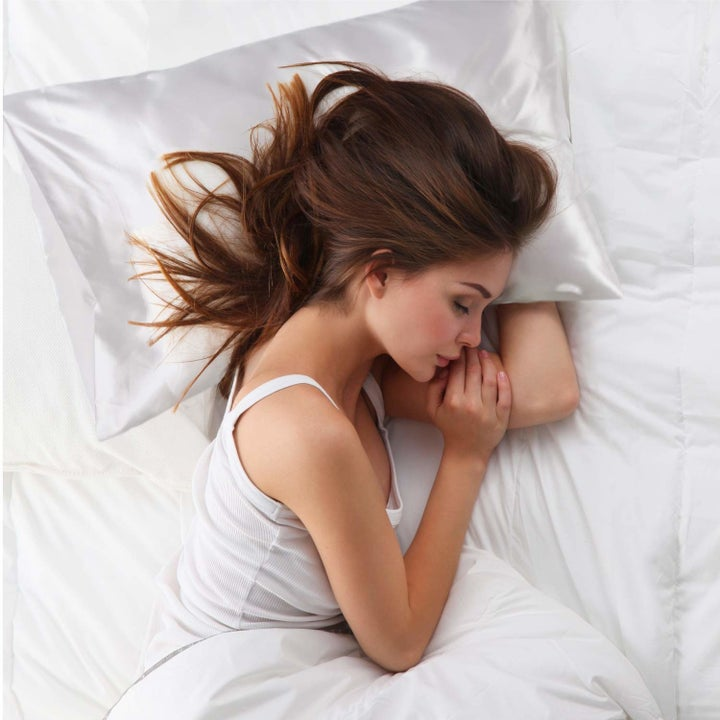 A person sleeping on one of the satin pillowcases.
