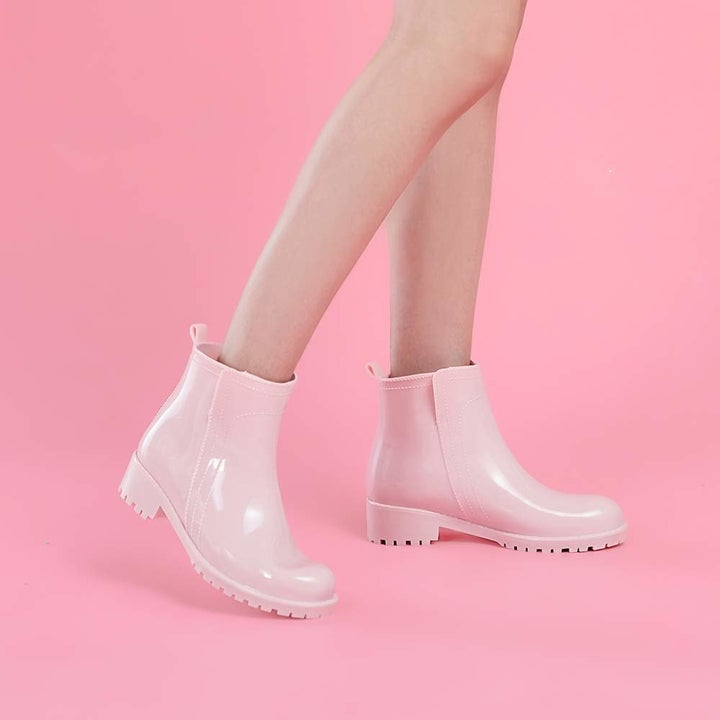 A model wearing the boots in pink.